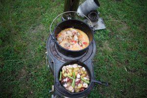 薪ストーブを使ってパエリアとアヒージョを料理している画像